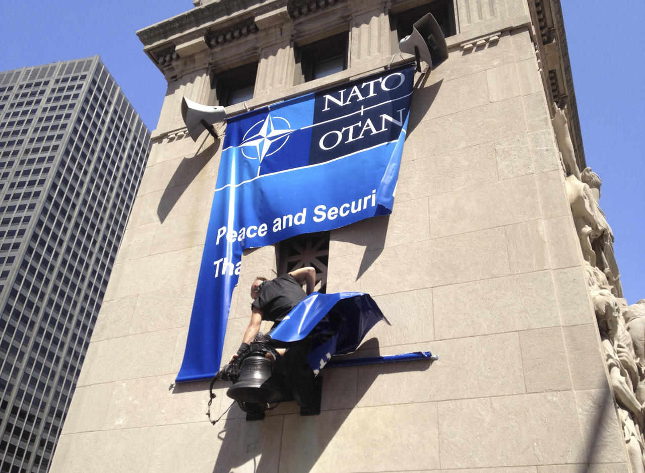 A protester tears down a NATO summit banner from one of the bridge towers along the Chicago River at the Michigan Ave. bridge in Chicago. Friday, May 18, 2012. (AP Photo/Nomaan Merchant)