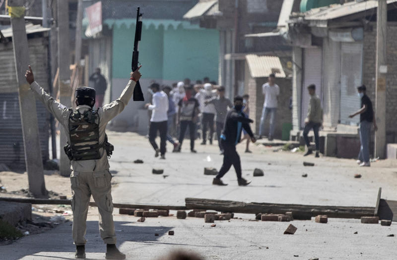 An Indian paramilitary soldier holds up a pellet gun as he challenges Kashmiri protesters marching on the streets in solidarity with rebels engaged in a gunbattle with soldiers, in Srinagar, Indian controlled Kashmir, Thursday, Sept. 17, 2020. The gunfight erupted shortly after scores of counterinsurgency police and soldiers launched an operation based on a tip about the presence of militants in a Srinagar neighborhood, Pankaj Singh, an Indian paramilitary spokesman, said. (AP Photo/Mukhtar Khan)