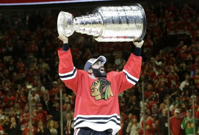 Chicago Blackhawks' Johnny Oduya raise the Stanley Cup on Monday, a game that produced disappointing ratings. (AP Photo/Nam Y. Huh)