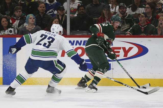Minnesota Wild's Eric Staal, right, controls the puck against Vancouver Canucks' Alexander Edler, of Sweden, in the second period of an NHL hockey game Sunday, Jan. 12, 2020, in St. Paul, Minn. (AP Photo/Stacy Bengs)