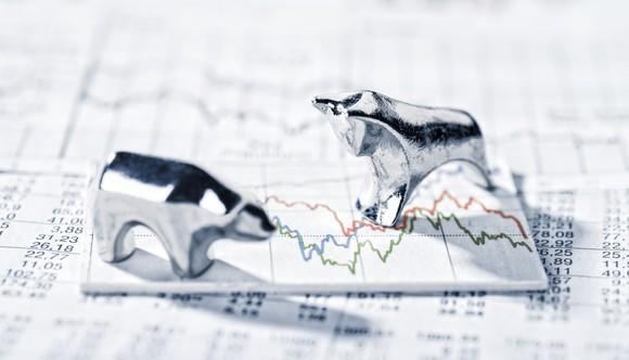 Small metallic bear and bull figurines standing on top of charts and figures.