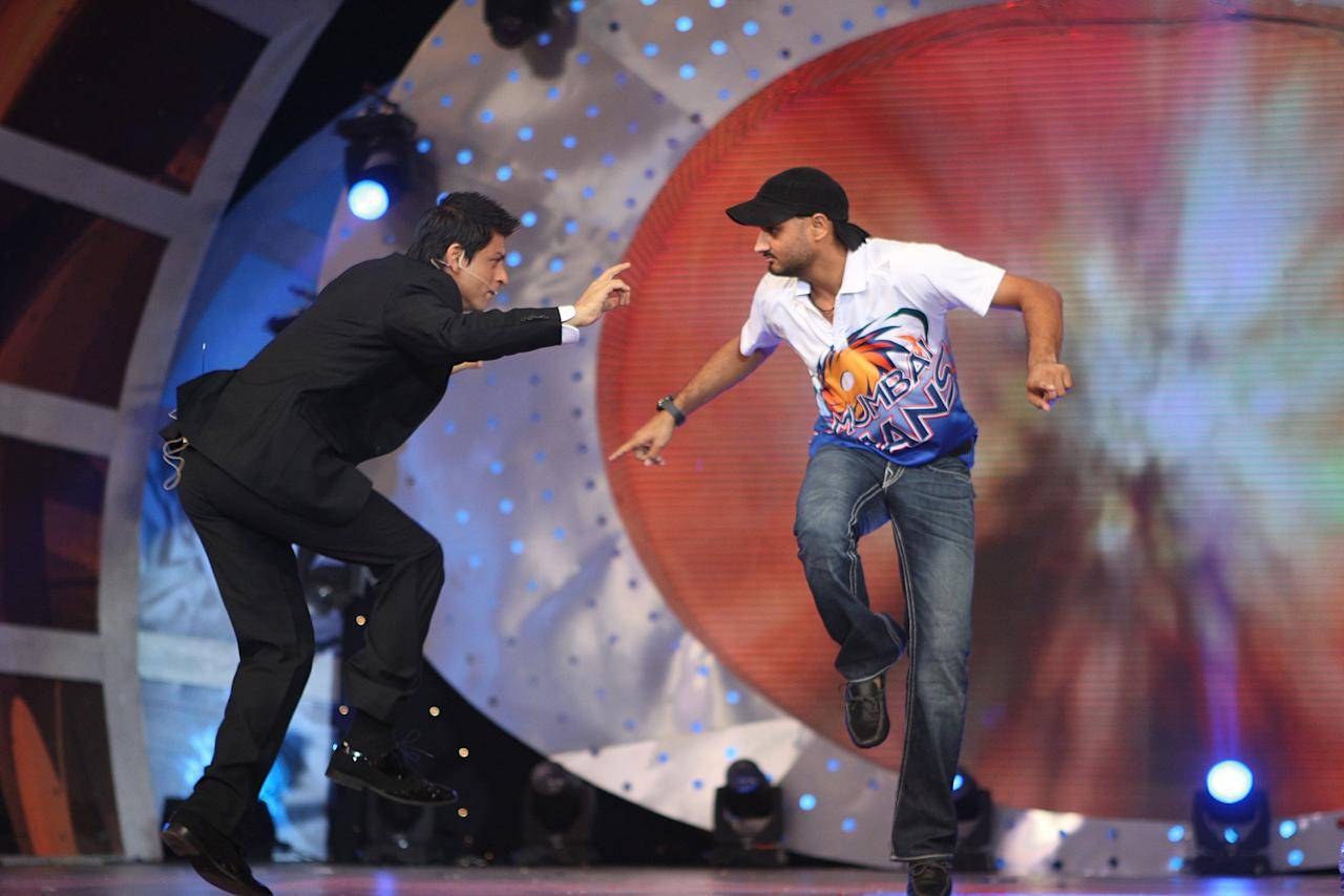 MUMBAI, INDIA - APRIL 23:  Harbhajan Singh (R) of Mumbai Indians performs on stage with actor Shahrukh Khan (L) at the IPL Awards Night at the Grand Hyatt on April 23, 2010 in Mumbai, India.  (Photo by Chirag Wakaskar-IPL 2010/IPL via Getty Images)