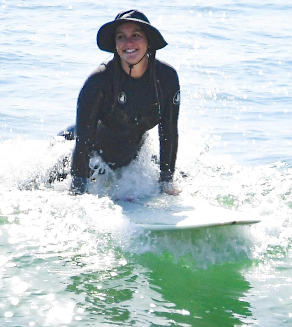 <p>Leighton Meester catches a wave during a surf session with husband Adam Brody on Monday in Malibu. </p>