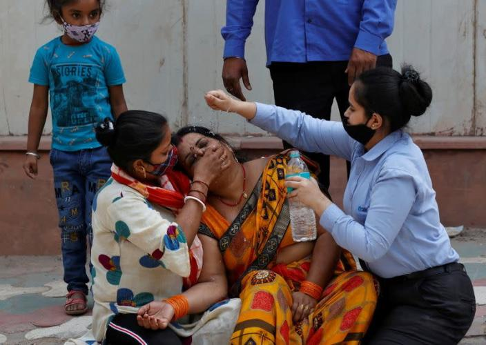 FILE PHOTO: A woman mourns after her father died due to the coronavirus disease (COVID-19) outside a mortuary of a COVID-19 hospital in New Delhi