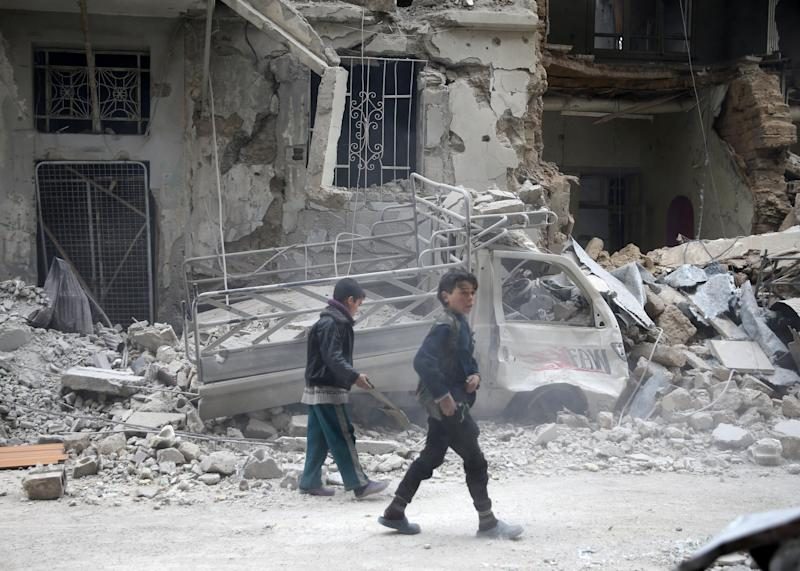 Children are inspect damages on a street in the besieged town of Douma, eastern Ghouta, in Damascus