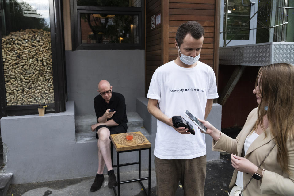 A waiter serves customers outside the Moments bar as they haven't got QR codes of vaccination or a negative coronavirus test in Moscow, Russia, Monday, June 28, 2021. Restaurants and cafes in Moscow on Monday began requesting that patrons provide proof of vaccination or a negative coronavirus test as the Russian capital faces a surge of new infections. As proof of vaccination for entering a restaurant, customers must visit a government website and get a QR code, a digital pattern designed to be read by a scanner. (AP Photo/Pavel Golovkin)