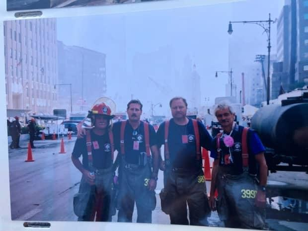 From left to right, Ottawa firefighters Brian Foley, Steve Carmichael, Gordie Thorpe and John Hamilton near the World Trade Center site days after 9/11. (Alistair Steele/CBC - image credit)