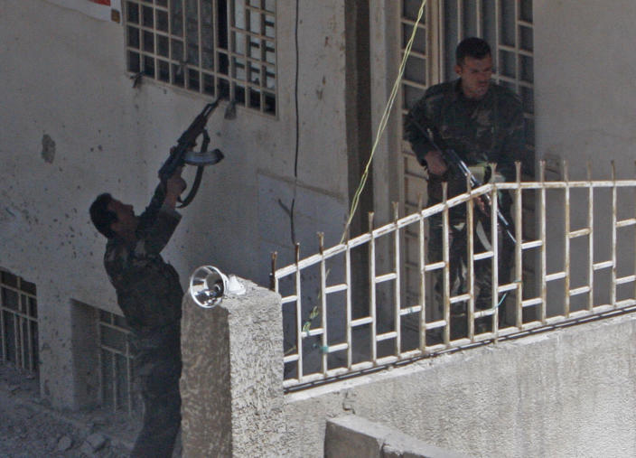Syrian army soldiers raid a building as they search for Syrian rebels in a suburb of Damascus, Syria, on Tuesday, March 20, 2012. An international human rights group accused Syria's armed opposition on Tuesday of carrying out serious abuses, including the kidnapping and torture of security forces, in a sign of the growing complexity of the year-old uprising against President Bashar Assad. (AP Photo)