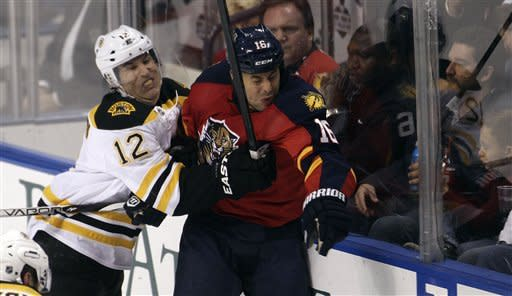 Boston Bruins' Brian Rolston (12) and Florida Panthers' Marco Sturm (16) slam into the glass during the first period of an NHL hockey game in Sunrise, Fla., Thursday, March 15, 2012. (AP Photo/J Pat Carter)