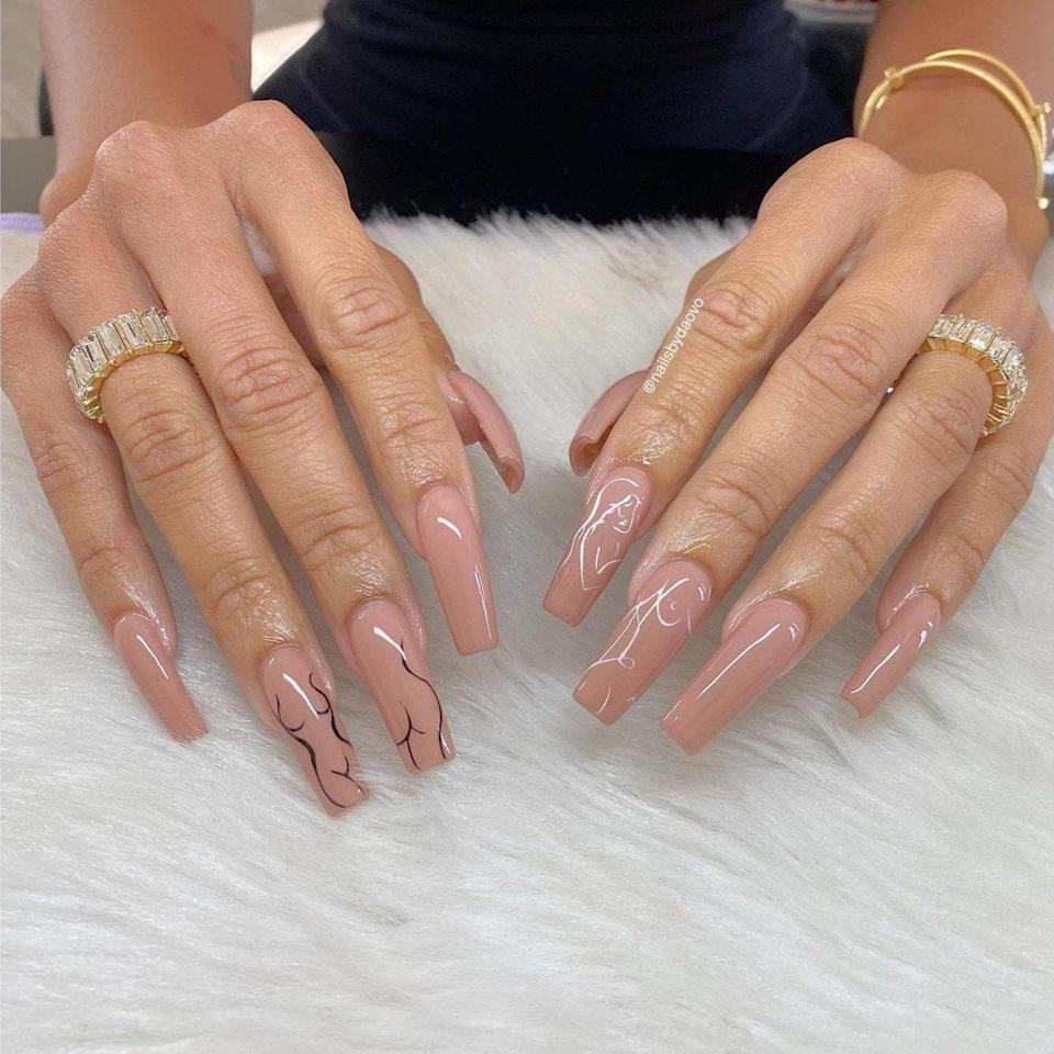 There are so many designs you can add to nude sets to spruce them up, like these square-shaped nails. Vo added the simple outlines of a curvy body on the middle and ring fingers on each hand. On one hand, they used black polish, while on the other, they used white.