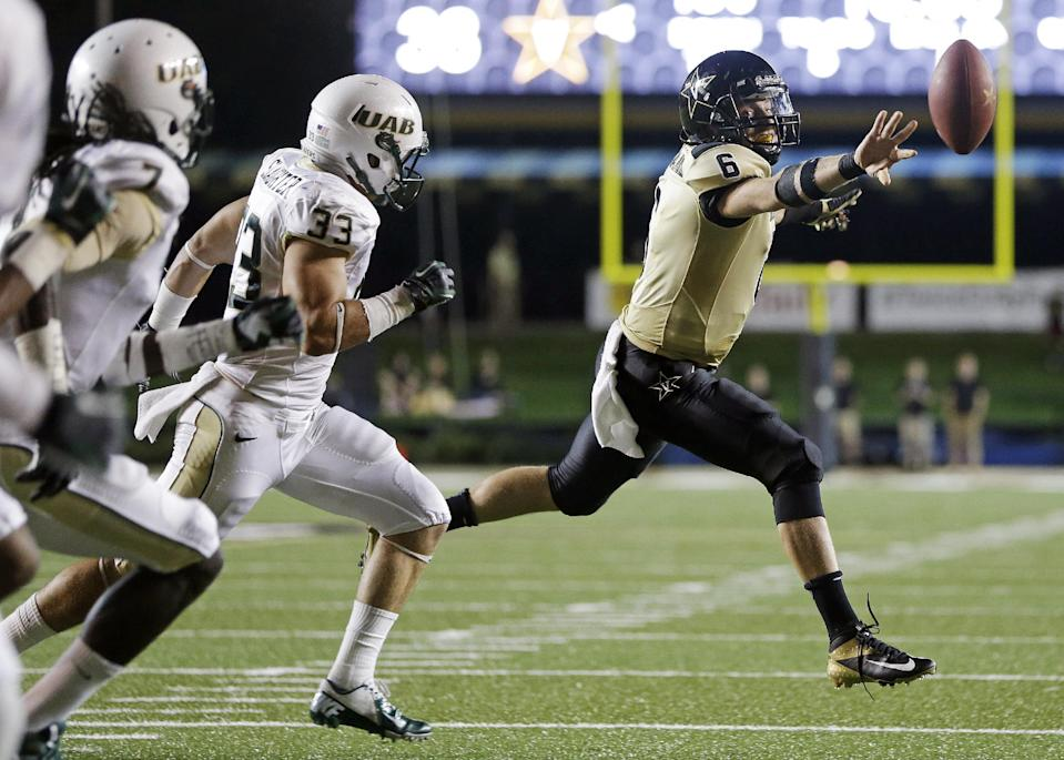 Vanderbilt quarterback Austyn Carta-Samuels (6) makes a 5-yard pass for a touchdown as he is chased by UAB defenders Derek Slaughter (33) and Jimmy Jean (7) in the fourth quarter of an NCAA college football game on Saturday, Sept. 28, 2013, in Nashville, Tenn. Vanderbilt won 52-24. (AP Photo/Mark Humphrey)