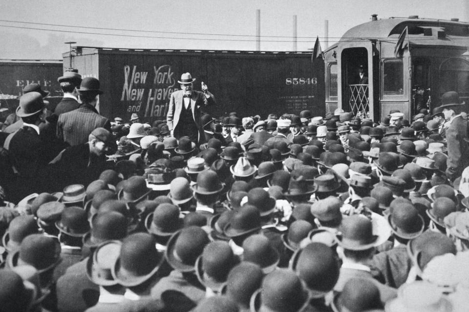 Black-and-white image of a man speaking from a train to a crowd of men in top hats