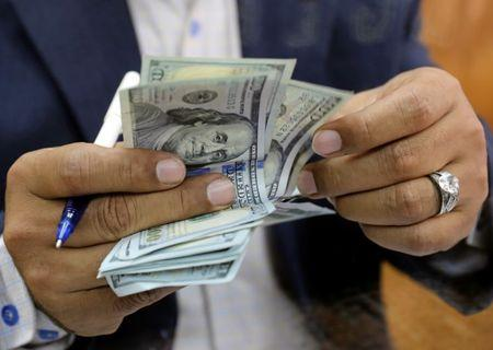 FILE PHOTO: A man counts U.S dollar bills at a money exchange office in central Cairo