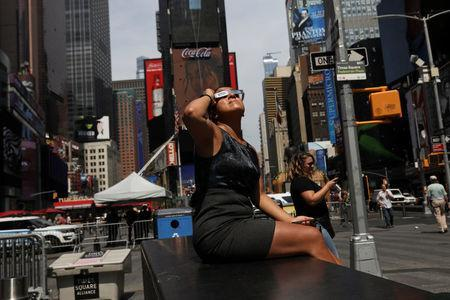 Jenney Vaverde, 42, views the solar eclipse at Times Square in Manhattan, New York, U.S., August 21, 2017. Location coordinates for this image are 40.7589° N, 73.9851° W. REUTERS/Shannon Stapleton
