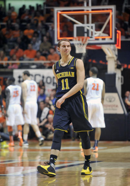 Michigan guard Nik Stauskas (11) looks over at Illinois fans after making a 3-point shot to end the first half of an NCAA college basketball game Tuesday, March 4, 2014, in Champaign, Ill. (AP Photo/Rick Danzl)