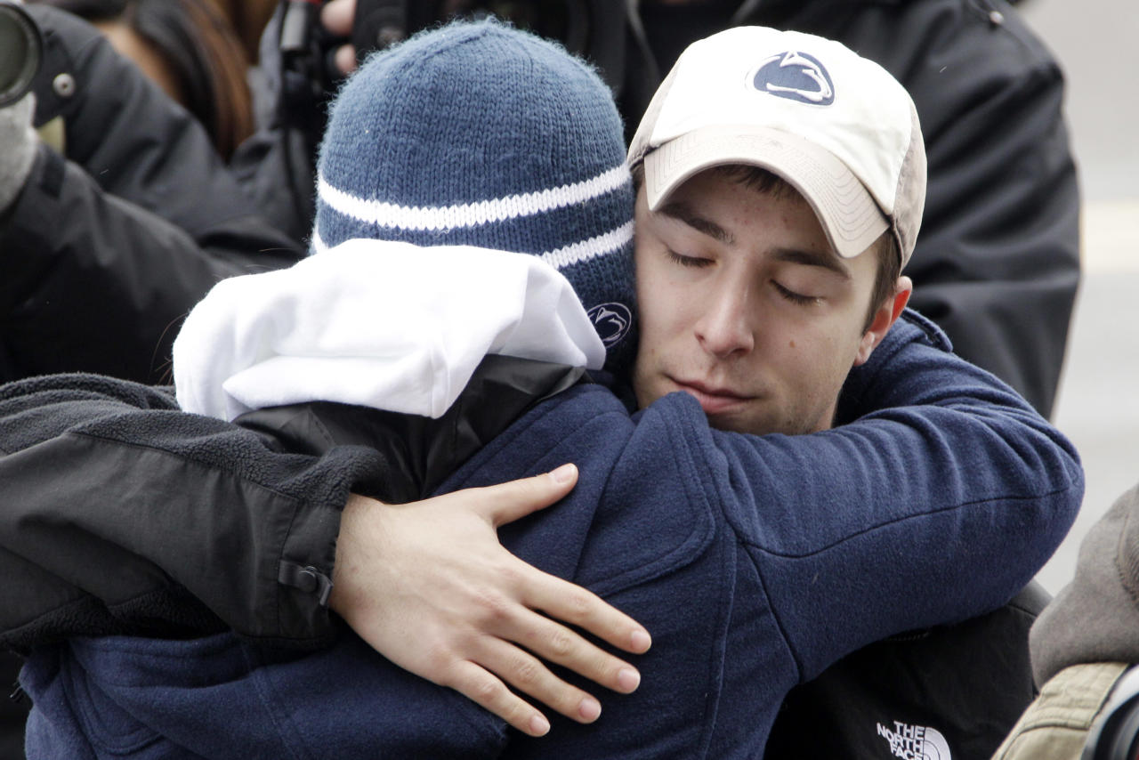 People gather around a statue of Joe Paterno outside Beaver Stadium on the Penn State University campus after learning of his death Sunday, Jan. 22, 2012, in State College, Pa. (AP Photo/Gene J. Puskar)