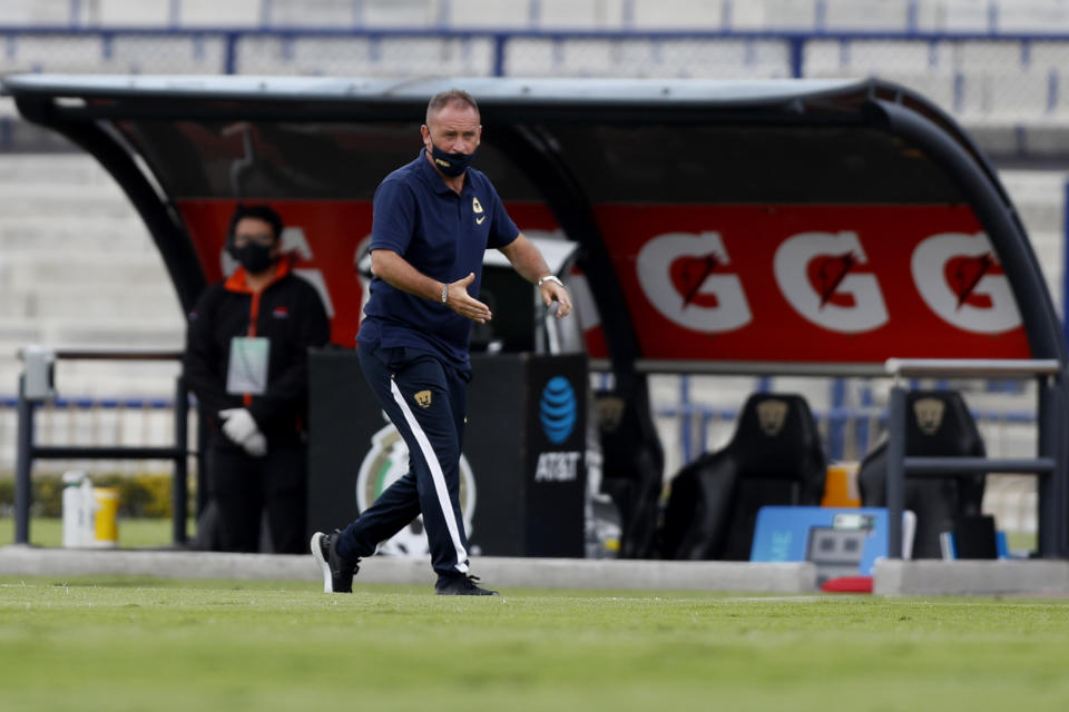Pumas' interim coach Andres Luciano Lillini, wearing a protective mask, gives instructions to his players during a Mexican soccer league match at University Olympic Stadium in Mexico City, Sunday, Aug. 9, 2020. The match was played without fans as a precaution against the coronavirus. (AP Photo/Eduardo Verdugo)