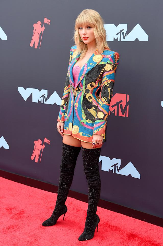 Taylor Swift, wearing Versace, boots by Christian Louboutin, and jewelry by Lorraine Schwartz.