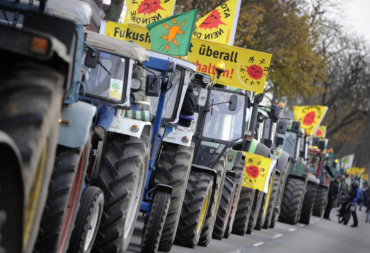 Farmers queue with their tractors near Gusborn, northern Germany, Saturday Nov. 26, 2011. They are on their way to a demonstration in Dannenberg, to protest against the transport and storage of nuclear waste in Germany. Vertical banner reads : Fukushima is everywhere. The shipment of nuclear waste reprocessed in France crossed into Germany Friday on its way to a controversial storage site in Gorleben that protesters say is unsafe. It is the first such shipment from France to Germany since Berlin decided to shut all its nuclear plants by 2022, following the disaster at Japan's Fukushima plant. The transport is due to arrive at the storage site on Sunday. (AP Photo/dapd/ Nigel Treblin)