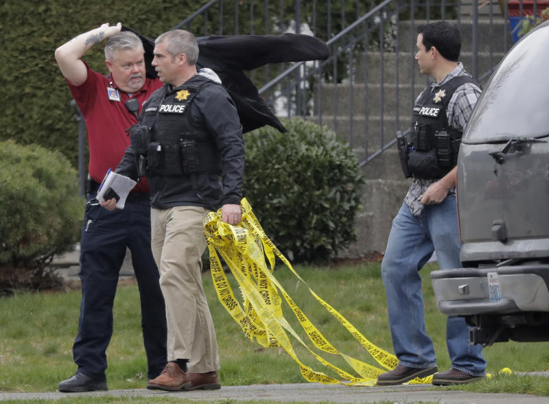 Officials carry crime scene tape, Tuesday, March 13, 2018, as they leave a home in Spanaway, Wash., where authorities say a member of the U.S. Air Force who was stationed at Joint Base Lewis-McChord fatally shot his two young children and their mother before killing himself overnight. (AP Photo/Ted S. Warren)