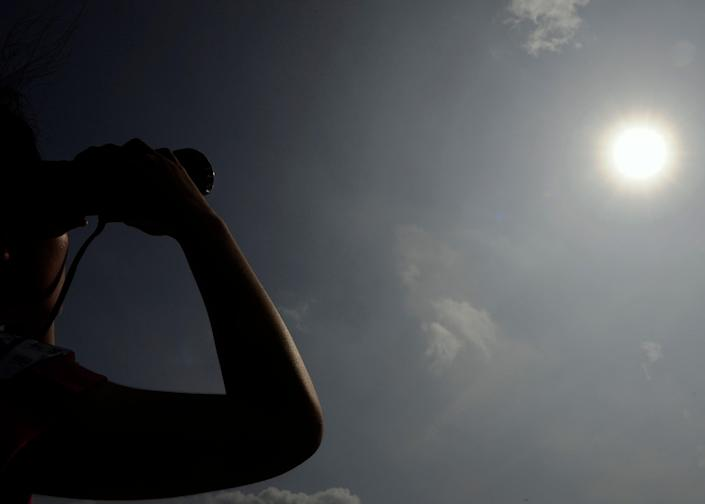 File image: A woman in Hong Kong looks through binoculars as planet Venus orbits between the Sun and the Earth during the transit of Venus on 6 June, 2012.  Earth's energy imbalance is the difference between the amount of energy it receives and from sun and radiates back  (AFP via Getty Images)