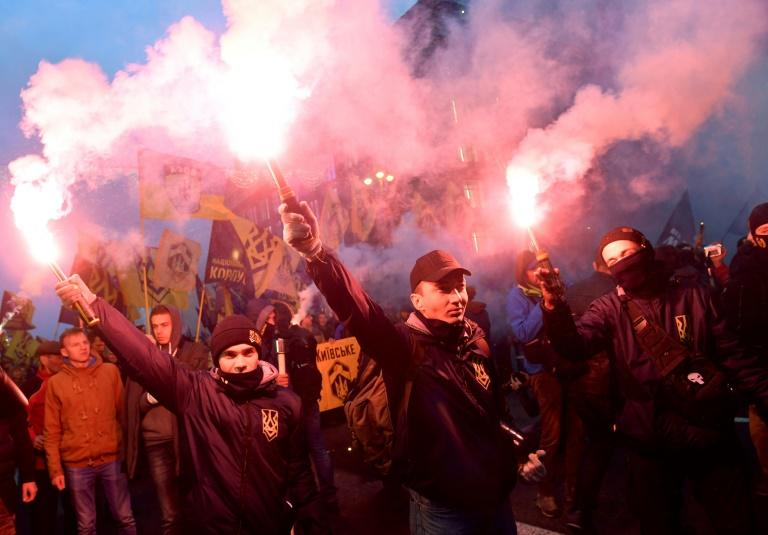 Ukrainian far-right activists hold flares during a march which also remembered the country's fallen soldiers in the east