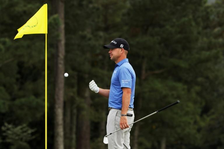 American Brian Harman, who shares second at the Masters, tosses his ball to his caddie on the 18th green at Augusta National on Friday