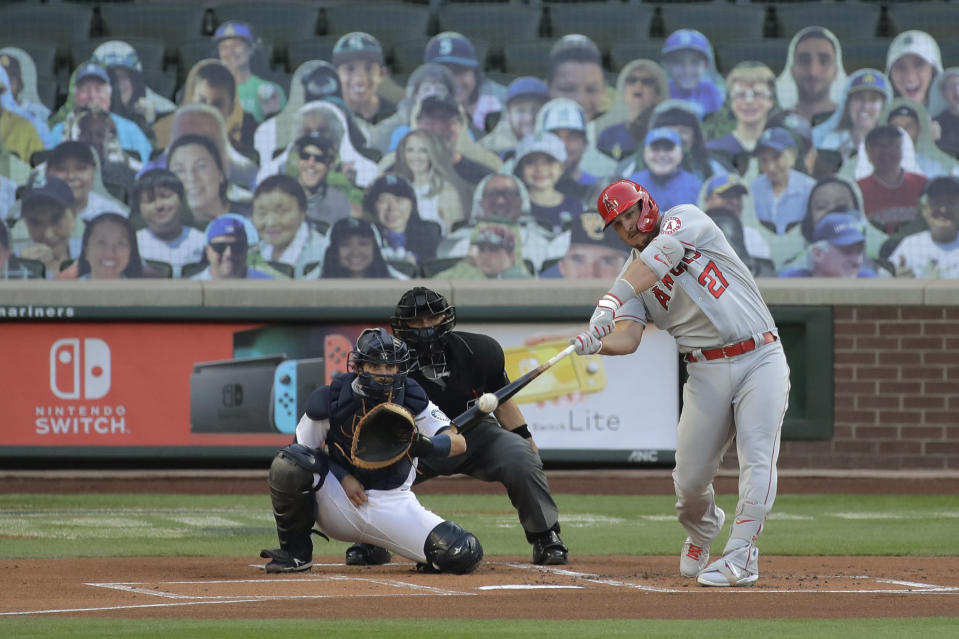 Los Angeles Angels' Mike Trout hits a solo home run during the first inning of a baseball game as Seattle Mariners catcher Austin Nola looks on, Tuesday, Aug. 4, 2020, in Seattle. (AP Photo/Ted S. Warren)