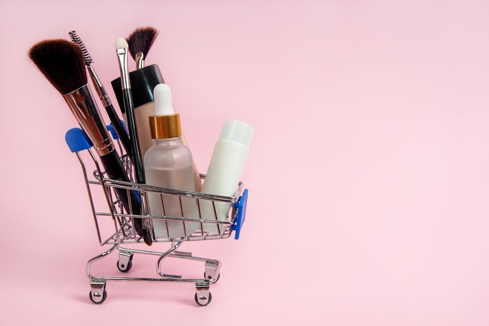 Skincare cosmetics and makeup brushes in a grocery shopping cart on a pink background. Skin care concept