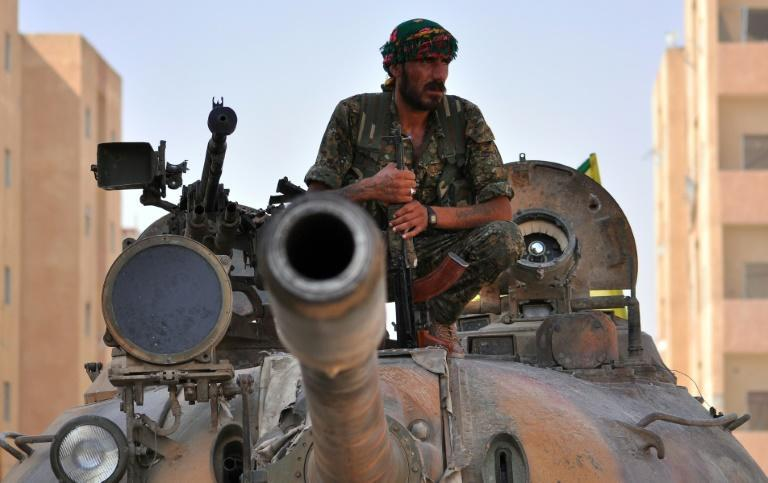A fighter from the Kurdish People's Protection Units (YPG) sits on a tank after they recaptured the northeastern city of Hasakeh from Islamic State militants on August 2, 2015