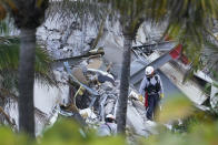 Rescue workers walk among the rubble where part of a 12-story beachfront condo building collapsed, Thursday, June 24, 2021, in Surfside, Fla. (AP Photo/Marta Lavandier)