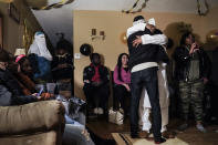 Myon Burrell, in white, gets a hug from a family member during a welcome home party following his release from prison, Tuesday, Dec. 15, 2020, in Minneapolis. Earlier in the day, Minnesota's pardon board commuted the sentence of Burrell, 34, a Black man who was sent to prison for life as a teen in a high-profile murder case that raised questions about the integrity of the criminal justice system. (AP Photo/John Minchillo)
