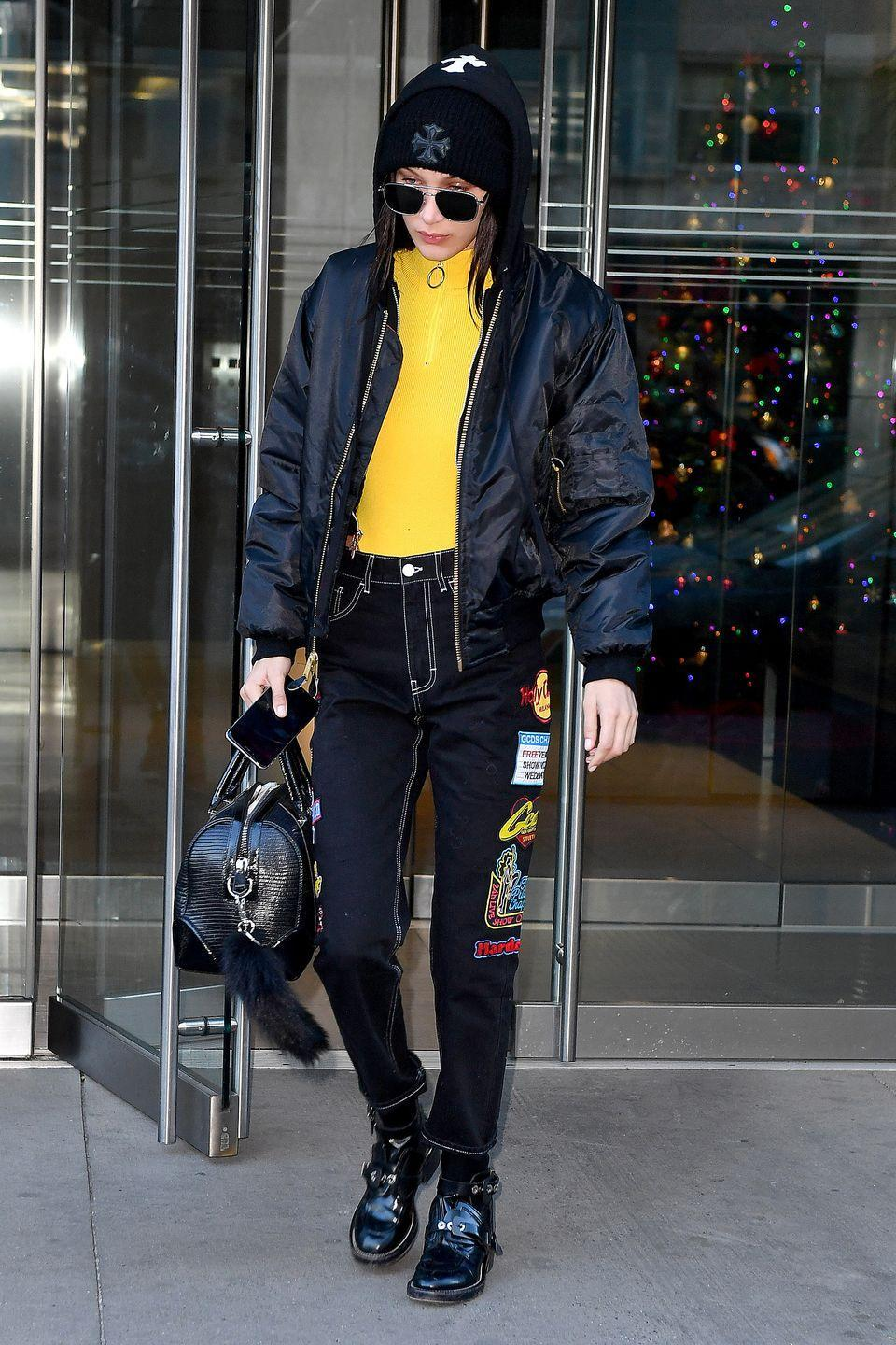 <p>In a black bomber jacket, hoodie, yellow zip-up top, beanie, sunglasses, embroidered dark jeans, patent buckled boots and a leather satchel while out in NYC.</p>