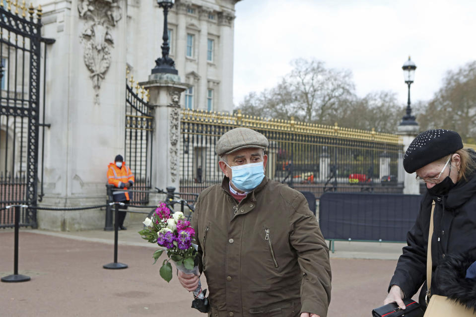 A man carries flowers outside Buckingham Palace, London, Monday, April 12, 2021. Britain's Prince Philip, the irascible and tough-minded husband of Queen Elizabeth II who spent more than seven decades supporting his wife in a role that mostly defined his life, died on Friday. (Luciana Guerra/PA via AP)