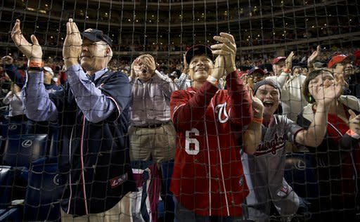 Washington Nationals fans celebrate after the Nationals clutched the National League East division title following a baseball game against the Philadelphia Phillies in Washington, Monday, Oct. 1, 2012. (AP Photo/Manuel Balce Ceneta)