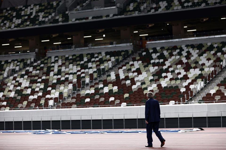FILE - In this Nov. 17, 2020, file photo, IOC President Thomas Bach looks at the empty stand during a visit to the National Stadium, the main venue for the Tokyo Olympic and Paralympic Games postponed until 2021 due to the coronavirus pandemic, in Tokyo. Tokyo Olympic organizers and the IOC on Saturday, March 20, 2021, announced a ban on fans from abroad attending the the games, which open on July 23. (Behrouz Mehri/Pool Photo via AP, File)