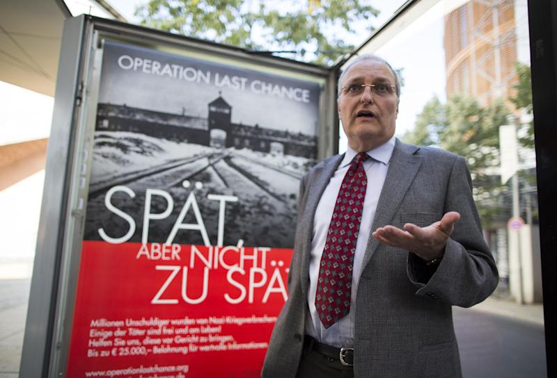 """Efraim Zuroff, the top Nazi-hunter of Simon Wiesenthal Center, talks to journalists as he stands in front of a placard reading """"Operation last chance - late but not too late"""" displayed in Berlin, Germany, Tuesday, July 23, 2013. With 2,000 placards in Berlin, Hamburg and Cologne cities the Simon Wiesenthal Center launched another campaign to find and prosecute Nazi war criminals while they are still alive. Efraim Zuroff, the center's top Nazi-hunter, told reporters in Berlin that """"Operation Last Chance II"""" would provide up to euro 25,000 (US$ 32,800) in reward money for information that leads to the investigation and prosecution of war criminals. (AP Photo/Gero Breloer)"""