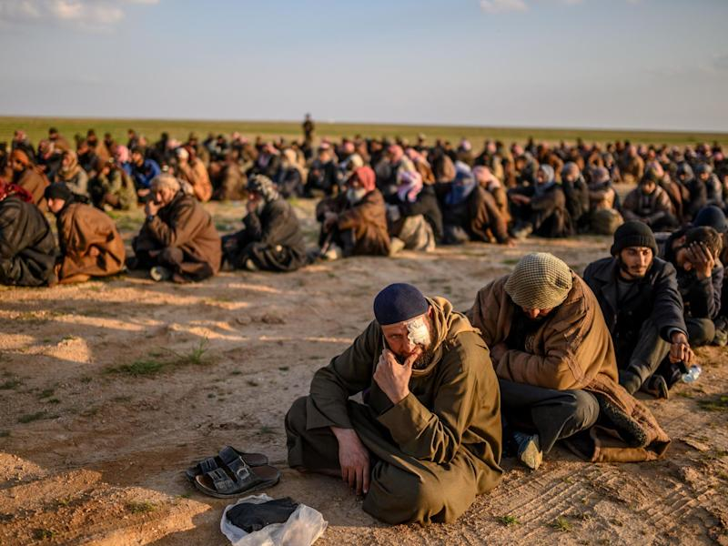 Suspected Isis fighters wait to be searched by the Kurdish-led SDF: AFP