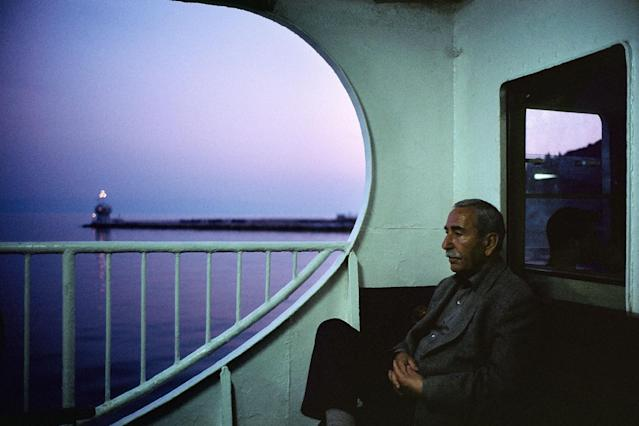 "<p>On board a ferry at dusk near the Princess Islands, Istanbul, Turkey, 2001. ""Over the course of seven years — from 1998 to 2005 —I wandered the streets of Istanbul, from Cihangir to Ayvansaray, from Üsküdar to Altin ehir, from Kadiköy to the ancient Theodosian walls. Meandering its warren of winding streets and riding its ferries, I found that serendipity guided me — in its roundabout way. More often than not, I had to lose my way in order to find my most successful photographs. In 2001, I remember crossing the Sea of Marmara after a frustrating series of missed ferries and lost opportunities — a typical afternoon for a street photographer. In the fading light, I thought I was done for the day, and was considering ordering a tea to help fend off the brisk sea air. Then something caught my eye: an older Turkish man, lost in thought, framed by the pink-purple glow of dusk. His reverie had a kind of mysterious weight to it — hard-to-define, yet almost palpable. In that moment, I slowly began to understand — at least visually — Orhan Pamuk's notion of 'hüzün,' an untranslatable word that suggests a rich and complicated melancholy that's unique to Istanbul, the writer's birthplace and one of the most astonishingly beautiful cities in the world, a place that seems haunted by its past, and, these days, beleaguered by its present."" (© Alex Webb/Magnum Photos) </p>"