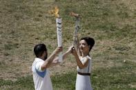 Greek actress Katerina Lehou, playing the role of High Priestess, passes the Olympic flame to a volunteer filling in for the first torch bearer, during the dress rehearsal for the Olympic flame lighting ceremony for the Rio 2016 Olympic Games at the site of ancient Olympia in Greece. REUTERS/Alkis Konstantinidis