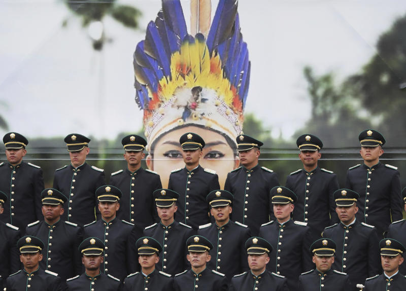 Newly graduated police cadets stand in formation in front of a large photograph of an indigenous police officer, during their graduation ceremony in Bogota, Colombia, Thursday, Nov. 7, 2019.  (AP Photo/Fernando Vergara)