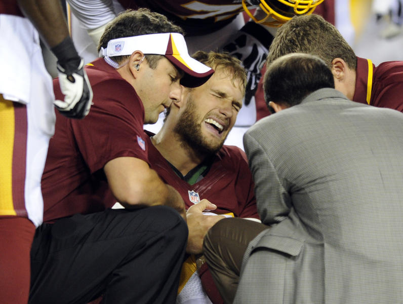 Washington Redskins quarterback Kirk Cousins, center, grimaces as Washington Redskins medical staff examine his foot during the first half of an NFL preseason football game against the Pittsburgh Steelers Monday, Aug. 19, 2013, in Landover, Md. (AP Photo/Nick Wass)