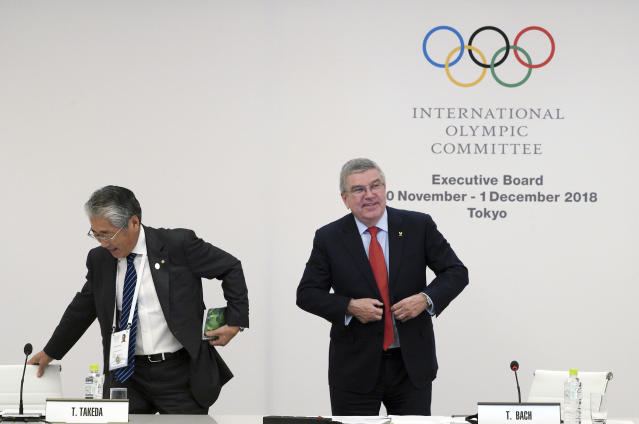 International Olympic Committee (IOC) President Thomas Bach, right, escorts Japanese Olympic Committee (JOC) President Tsunekazu Takeda during an IOC Executive Board meeting in Tokyo Friday, Nov. 30, 2018. The focus of the meeting was a decision on what to do with boxings corruption-plagued international federation. (AP Photo/Eugene Hoshiko)