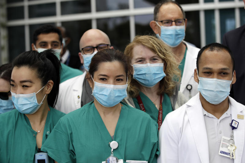 FILE - In this April 17, 2020 file photo Hospital personnel stand outside Providence St. John's Medical Center in Santa Monica, Calif. Three million surgical masks arrived in California last weekend as the first shipment in a major deal cut by California Gov. Gavin Newsom for 200 million masks per month to protect health care and other workers from the coronavirus. (AP Photo/Marcio Jose Sanchez,File)