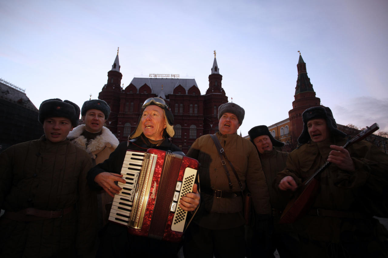 Members of Russian historical clubs dressed in Red Army World War II uniform sing as one of them play accordion before a parade in Red Square in Moscow, Russia, early Monday, Nov. 7, 2011. The parade marks the 70th anniversary of a November 7 parade on Red Square when soldiers went directly to the front during World War II. November 7 for decades was a holiday celebrating the 1917 Bolshevik Revolution.(AP Photo/Alexander Zemlianichenko Jr)