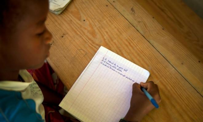 A boy takes notes during a Creole class at the Louverture Cleary School in Haiti, Jan. 24.
