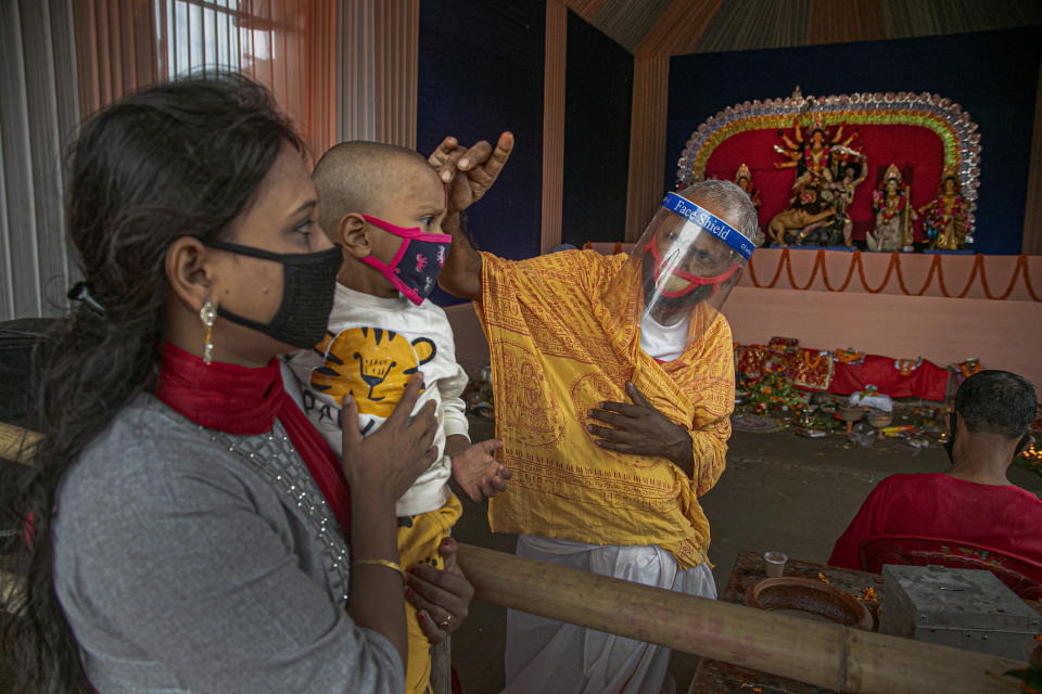 A Hindu priest wearing a face shield applies vermilion paste on the forehead of a child during Durga Puja festival in Gauhati, India, Saturday, Oct. 24, 2020. Weeks after India fully opened up from a harsh lockdown and began to modestly turn a corner by cutting new infections by near half, a Hindu festival season is raising fears that the disease could spoil the hard-won gains. Health experts worry the festivals can set off a whole new cascade of infections, further testing and straining India's battered health care system. (AP Photo/Anupam Nath)