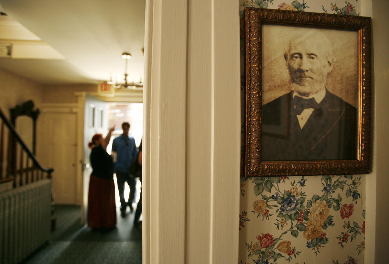 A photograph of Lizzie Borden's  father Andrew Borden, right, hangs in the room where he was killed in the infamous 1892 double murder, in Fall River, Mass., Wednesday, Aug. 20, 2008. The owner of the Lizzie  Borden Bed and Breakfast and gift shop in Fall River has filed a federal lawsuit to prevent a new museum and shop in Salem from using the name of the former Sunday school teacher who was accused in the hatchet deaths of her wealthy father and stepmother. (AP Photo/Steven Senne)