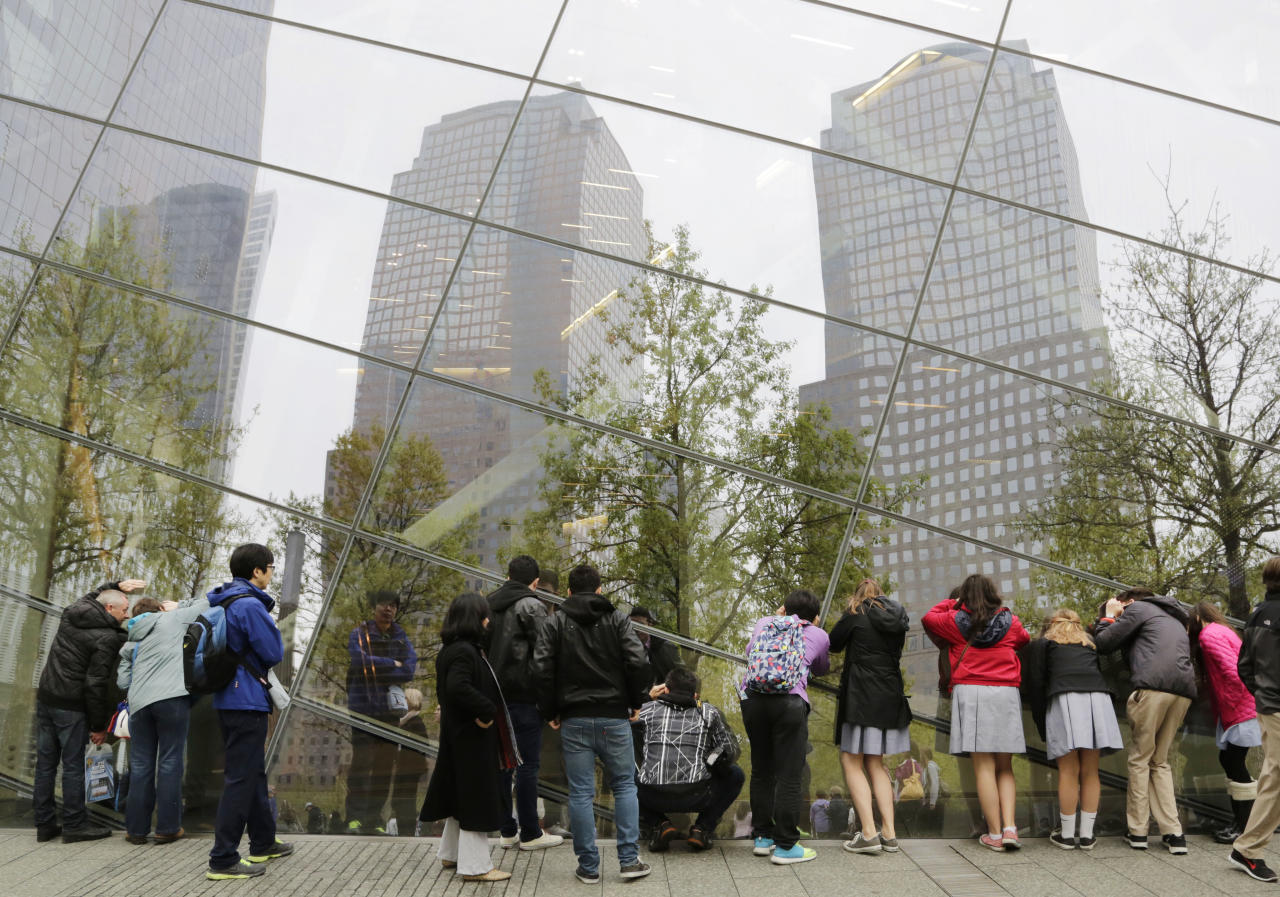 Visitors to the National September 11 Memorial & Museum peer through the windows of the museum, Thursday, May 8, 2014 at the World Trade Center in New York. The unidentified remains of those killed in the attacks of Sept. 11, 2001 are set to be moved Saturday to a repository beneath the memorial and museum. (AP Photo/Mark Lennihan)