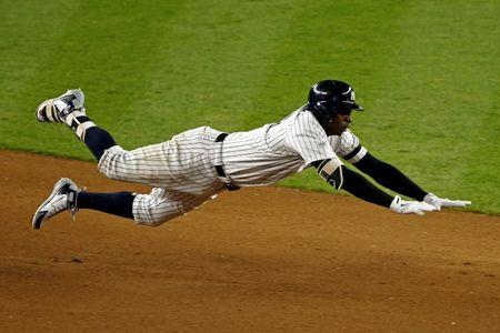Oct 18, 2017; Bronx, NY, USA; New York Yankees shortstop Didi Gregorius (18) dives into second base for a double during the seventh inning against the Houston Astros in game five of the 2017 ALCS playoff baseball series at Yankee Stadium. Mandatory Credit: Adam Hunger-USA TODAY Sports